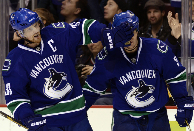 VANCOUVER, CANADA - DECEMBER 26: Kevin Bieksa #3 of the Vancouver Canucks is gets a friendly face wash from Henrik Sedin #33 after scoring what proved to be the game winning goal in a 3-2 win against the Edmonton Oilers during the third period in NHL acti