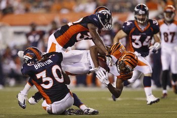 CINCINNATI, OH - AUGUST 15: Jerome Simpson #89 of the Cincinnati Bengals gets tackled after catching a pass by Perrish Cox #32 and David Bruton #30 of the Denver Broncos during a preseason game at Paul Brown Stadium on August 15, 2010 in Cincinnati, Ohio.