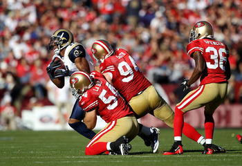 SAN FRANCISCO - NOVEMBER 14:  Brandon Gibson #11 of the St. Louis Rams is tackled by Travis LaBoy #54 and Justin Smith #94 of the San Francisco 49ers at Candlestick Park on November 14, 2010 in San Francisco, California.  (Photo by Ezra Shaw/Getty Images)