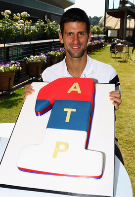 LONDON, ENGLAND - JULY 04: (EXCLUSIVE COVERAGE) Novak Djokovic of Serbia poses with a cake decorated in the colours of the Serbian flag as he celebrates becoming the new World number one tennis player on July 4, 2011 in London, England.  (Photo by Clive B