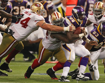 MINNEAPOLIS - SEPTEMBER 27: Adrian Peterson #28 of the Minnesota Vikings is tackled by Aubrayo Franklin #92 and Justin Smith #94 of the San Francisco 49ers at the Hubert H. Humphrey Metrodome on September 27, 2009 in Minneapolis, Minnesota. The Vikings de