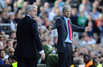 LONDON, ENGLAND - MAY 22:  Arsene Wenger of Arsenal shows his emotions as Mark Hughes of Fulham looks on during the Barclays Premier League match between Fulham and Arsenal at Craven Cottage on May 22, 2011 in London, England.  (Photo by Clive Mason/Getty