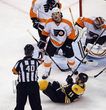 BOSTON, MA - MAY 06: Daniel Carcillo #13 of the Philadelphia Flyers gets a cross checking penalty against Gregory Campbell #11 of the Boston Bruins   in Game Four of the Eastern Conference Semifinals during the 2011 NHL Stanley Cup Playoffs at TD Garden o