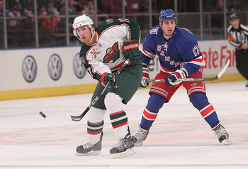 NEW YORK, NY - MARCH 03: John Madden #11 of the Minnesota Wild passes the puck in front of Brandon Dubinsky #17 of the New York Rangers at Madison Square Garden on March 3, 2011 in New York City.  (Photo by Nick Laham/Getty Images)
