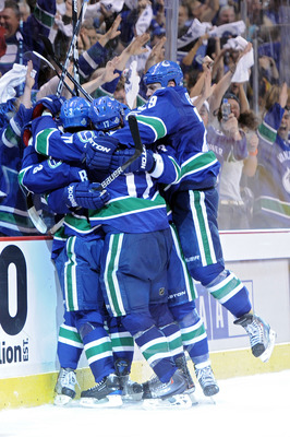 VANCOUVER, BC - JUNE 01:  Raffi Torres #13 of the Vancouver Canucks celebrates with his teammates Kevin Bieksa #3, Ryan Kesler #17 and Aaron Rome #29 after he scored a goal late in the third period against Tim Thomas #30 of the Boston Bruins during game o