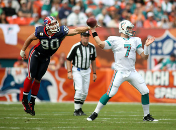 MIAMI, FL - DECEMBER 19:  Quarterback Chad Henne #7 of the Miami Dolphins is pressured by Linebacker Chris Kelsay #90 of the Buffalo Bills during a game at Sun Life Stadium on December 19, 2010 in Miami, Florida. The Bills defeated the Dolphins 17-14.  (P