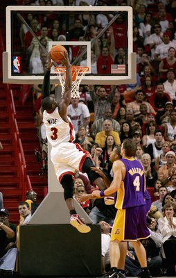 MIAMI - DECEMBER 25:  Dwyane Wade #3 of the Miami Heat goes in for a slam dunk over Luke Walton #4 of the Los Angeles Lakers during the game on December 25, 2006 at the American Airlines Arena in Miami, Florida.  The Heat won 101-85.  NOTE TO USER: User e