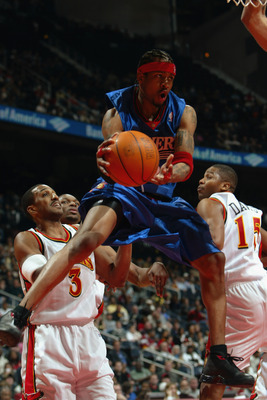 ATLANTA - DECEMBER 21:  Allen Iverson #3 of the Philadelphia 76ers goes to the basket while being pressured by Shareef Abdur-Rahim #3 (L) and Emanual Davis #15 (R) of the Atlanta Hawks during the game at Philips Arena on December 21, 2002 in Atlanta, Geor