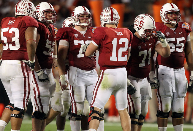 MIAMI, FL - JANUARY 03: Quarterback Andrew Luck #12 of the Stanford Cardinal calls a play in the huddle as Derek Hall #53, David DeCastro #52, Chase Beeler #72, Andrew Phillips #71 and Jonathan Martin #55 listen to the call against the Virginia Tech Hokie