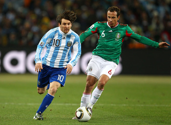 JOHANNESBURG, SOUTH AFRICA - JUNE 27:  Lionel Messi of Argentina goes past Gerardo Torrado of Mexico during the 2010 FIFA World Cup South Africa Round of Sixteen match between Argentina and Mexico at Soccer City Stadium on June 27, 2010 in Johannesburg, S