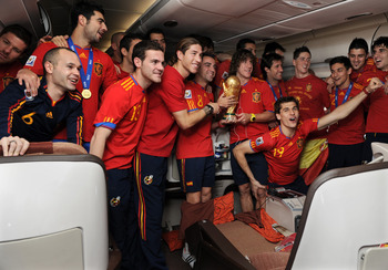UNSPECIFIED - JULY 12: (L-R) Andres Iniesta, Raul Albiol, Juan Manuel Mata, Sergio Ramos, Xavi Hernandez, Carles Puyol, Fernando Llorente, Fernando Torres, Jesus Navas and David Villa of Spain celebrate with the World Cup trophy during the Spanish team's