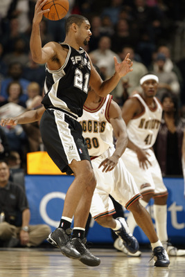 DENVER - NOVEMBER 26:  Tim Duncan #21 of the San Antonio Spurs is defended by Mark Blount #30 of the Denver Nuggets during the game at Pepsi Center on November 26, 2002 in Denver, Colorado.  The Nuggets won 85-81.   NOTE TO USER: User expressly acknowledg