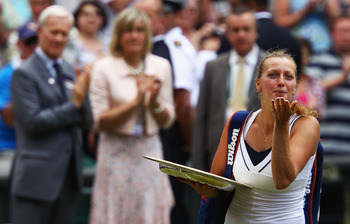 LONDON, ENGLAND - JULY 02:  Petra Kvitova of the Czech Republic holds her Championship trophy and blows a kiss to the crowd as she walks off court after winning her Ladies' final round match against Maria Sharapova of Russia on Day Twelve of the Wimbledon