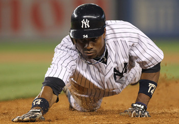 NEW YORK, NY - JUNE 09:  Curtis Granderson #14 of the New York Yankees dives safely into first against the Boston Red Sox on June 9, 2011 at Yankee Stadium in the Bronx borough of New York City.  (Photo by Nick Laham/Getty Images)