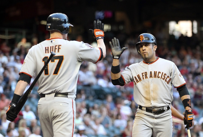 PHOENIX, AZ - JUNE 14:  Andres Torres #56 of the San Francisco Giants high fives teammate Aubrey Huff #17 after scoring against the Arizona Diamondbacks during the first inning of the Major League Baseball game at Chase Field on June 14, 2011 in Phoenix,