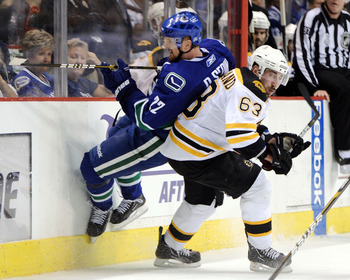 VANCOUVER, BC - JUNE 15:  Brad Marchand #63 of the Boston Bruins checks Daniel Sedin #22 of the Vancouver Canucks during Game Seven of the 2011 NHL Stanley Cup Final at Rogers Arena on June 15, 2011 in Vancouver, British Columbia, Canada.  (Photo by Harry
