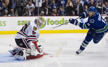 VANCOUVER, CANADA - APRIL 26: Goalie Corey Crawford #50 of the Chicago Blackhawks stops the puck in a penalty shot taken by Alexandre Burrows #14 of the Vancouver Canucks during the third period in Game Seven of the Western Conference Quarterfinals in the