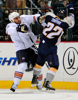 NASHVILLE, TN - MARCH 22:  Theo Peckham #49 of the Edmonton Oilers checks Jordin Tootoo #22 of the Nashville Predators on March 22, 2011 at the Bridgestone Arena in Nashville, Tennessee.  (Photo by Frederick Breedon/Getty Images)