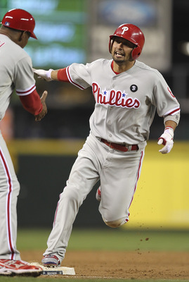 SEATTLE - JUNE 18:  Shane Victorino #8 of the Philadelphia Phillies is congratulated by third base coach Juan Samuel #12 after hitting a two-run homer in the ninth inning against the Seattle Mariners at Safeco Field on June 18, 2011 in Seattle, Washington