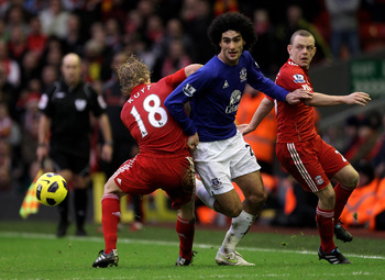 LIVERPOOL, ENGLAND - JANUARY 16:  Marouane Fellaini of Everton is challenged by Jay Spearing and Dirk Kuyt of Liverpool during the Barclays Premier League match between Liverpool and Everton at Anfield on January 16, 2011 in Liverpool, England.  (Photo by