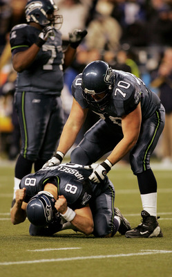 SEATTLE - JANUARY 8:   Lineman Jerry Wunsch #70 of the Seattle Seahawks helps a grieving quarterback Matt Hasselbeck #8 to his feet after Hasselbeck threw an incomplete pass into the endzone on their final offensive play as the Seahawks were defeated by t