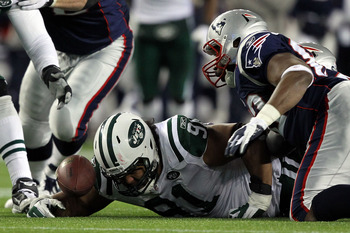 FOXBORO, MA - JANUARY 16: Sione Pouha #91 of the New York Jets and Alge Crumpler #82 of the New England Patriots fight to recover a fumble by Tom Brady #12 of the New England Patriots of the New York Jets against during their 2011 AFC divisional playoff g
