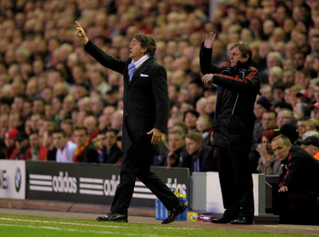 LIVERPOOL, ENGLAND - APRIL 11:  Manchester City Manager Roberto Mancini and Liverpool Manager Kenny Dalglish (R) issue instructions during the Barclays Premier League match between Liverpool and Manchester City at Anfield on April 11, 2011 in Liverpool, E