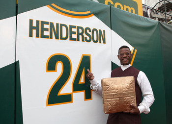 OAKLAND, CA - AUGUST 01:  Hall of Fame baseball player Rickey Henderson stands in front of his retired jersey during a ceremony to retire his number 24 by the Oakland Athletics before the start of the game against the Toronto Blue Jays August 1, 2009 at t