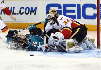 SAN JOSE, CA - MARCH 23:  Devin Setoguchi #16 of the San Jose Sharks collides with goalie  Miikka Kiprusoff #34 of the Calgary Flames at the HP Pavilion on March 23, 2011 in San Jose, California.  (Photo by Ezra Shaw/Getty Images)