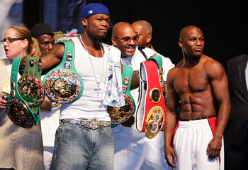 LAS VEGAS - MAY 04:  (L) Rapper 50 Cent holds up Floyd Mayweather Jr. belts at the weigh-in alongside manager Leonard Ellerbe (M) and Floyd Mayweather Jr (R) at the MGM Grand Garden Arena May 4, 2007 in Las Vegas, Nevada. Mayweather Jr. will fight Oscar D