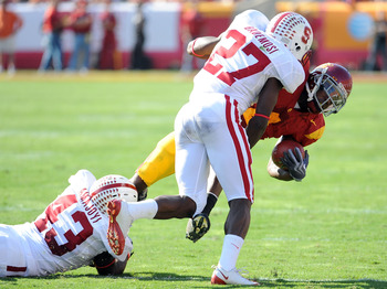 LOS ANGELES, CA - NOVEMBER 14:  Joe McKnight #4 of the USC Trojans is tackled by Johnson Bademosi #27 and Chike Amajoyi #43 of the Stanford Cardinal during the first half at the Los Angeles Memorial Coliseum on November 14, 2009 in Los Angeles, California