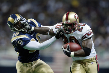 ST. LOUIS - DECEMBER 30:  Running back Garrison Hearst #20 of the San Francisco 49ers carries the ball as he gives a stiff right arm to defensive back Kim Herring #20 of the St. Louis Rams on December 30, 2002 at the Edward Jones Dome in St. Louis, Missou