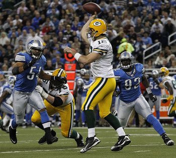 DETROIT - DECEMBER 12: Aaron Rogers #12 of the Green Bay Packers drops back to pass as DeAndre Levy #54 and Cliff Avrill #92 of the Detroit Lions rush the passer during the second quarter of the game against the Detroit Lions at Ford Field on December 12,