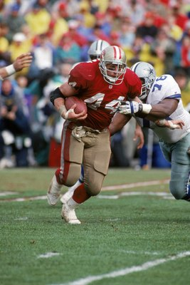 SAN FRANCISCO - JANUARY 17:  Full back Tom Rathman #44 of the San Francisco 49ers battles for yards against the Dallas Cowboys defense during the 1992 NFC Championship Game at Candlestick Park on January 17, 1993 in San Francisco, California.  The Cowboys