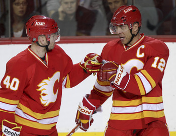 CALGARY, CANADA - APRIL 6:Jarome Iginla #12 of the Calgary Flames is congratulated by teammate Alex Tanguay #40 on his hat trick goal against  the Edmonton Oilers in third period NHL action on April 6, 2011 at the Scotiabank Saddledome in Calgary, Alberta