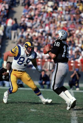 LOS ANGELES - DECEMBER 18:  Quarterback Jim Plunkett #16 of the Los Angeles Raiders looks down field for a receivers as he gets rushed by Los Angeles Rams defensive end Jack Youngblood #85 during a game at Los Angeles Memorial Coliseum on December 18, 198
