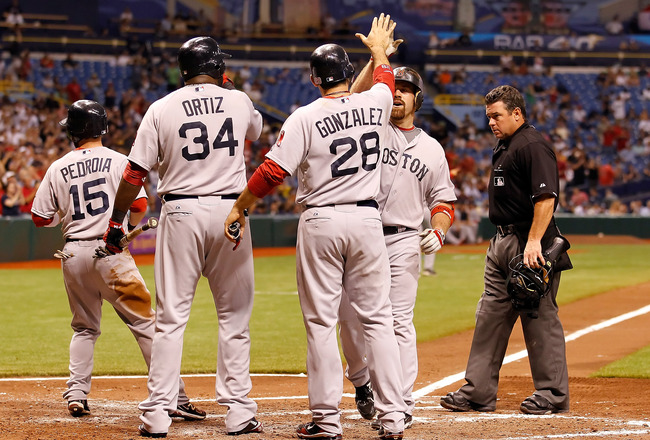 ST PETERSBURG, FL - JUNE 15:  Infielder Kevin Youkilis #20 of the Boston Red Sox is congratulated by Adrian Gonzalez #28, David Ortiz #34 and Dustin Pedroia #15 after his three run home run in the seventh inning against the Tampa Bay Rays during the game