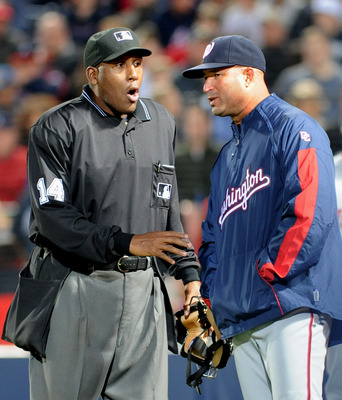 ATLANTA - APRIL 11: Home plate umpire Chuck Meriwether explains a call to manager Manny Acta #14 of the Washington Nationals during play against the Atlanta Braves April 11, 2009 at Turner Field in Atlanta, Georgia.  (Photo by Al Messerschmidt/Getty Image