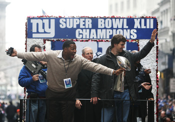 NEW YORK - FEBRUARY 05:  (L-R) Michael Strahan, Head coach Tom Coughlin and Eli Manning of the New York Giants ride in a float along Broadway, also known as 'The Canyon of Heroes' during Super Bowl XLII victory parade in New York City.  (Photo by Al Bello
