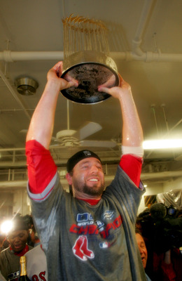 ST LOUIS - OCTOBER 27:  Kevin Millar #15 of the Boston Red Sox celebrates with the Championship trophy in the locker room after defeating the St. Louis Cardinals 3-0 to win game four of the World Series on October 27, 2004 at Busch Stadium in St. Louis, M