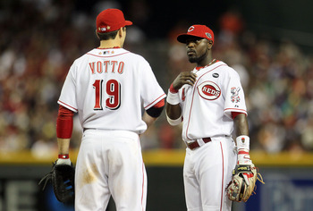 PHOENIX, AZ - JULY 12:  National League All-Star Joey Votto #19 of the Cincinnati Reds speaks with teammate National League All-Star Brandon Phillips #4 of the Cincinnati Reds during the 82nd MLB All-Star Game at Chase Field on July 12, 2011 in Phoenix, A