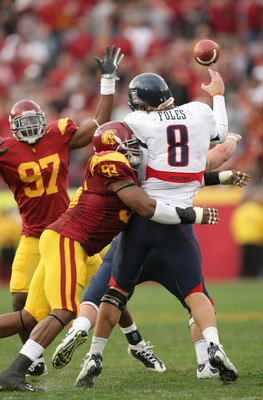 LOS ANGELES, CA - DECEMBER 05:  Quarterback Nick Foles #8 of the Arizona Wildcats is hit as he throws a pass by defensive end Everson Griffen #93 of the USC Trojans on December 5, 2009 at the Los Angeles Coliseum in Los Angeles, California. Arizona won 21