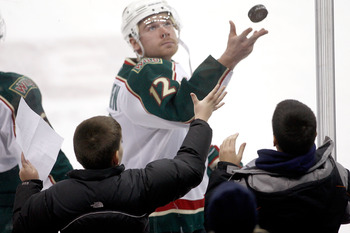 COLUMBUS, OH - DECEMBER 27:  Chuck Kobasew #12 of the Minnesota Wild tosses a puck over the glass to a fan during warmups prior to the start of the game against the Columbus Blue Jackets on December 27, 2010 at Nationwide Arena in Columbus, Ohio.  (Photo