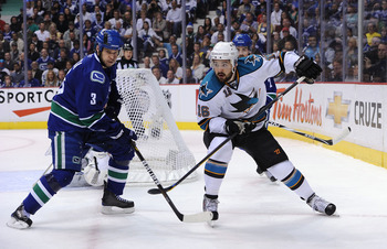 VANCOUVER, CANADA - MAY 24:  Devin Setoguchi #16 of the San Jose Sharks looks to play the puck as Kevin Bieksa #3 of the Vancouver Canucks defends the play in Game Five of the Western Conference Finals during the 2011 Stanley Cup Playoffs at Rogers Arena