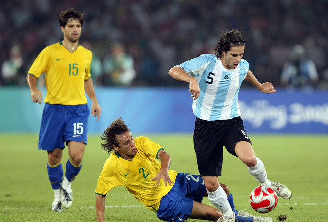 BEIJING - AUGUST 19:  Fernando Gago of Argentina skips away from Rafinha of Brazil during the men's football semifinal match between Argentina and Brazil at Workers' Stadium on Day 11 of the Beijing 2008 Olympic Games on August 19, 2008 in Beijing, China.