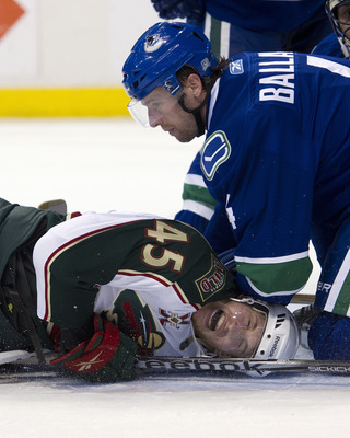 VANCOUVER, CANADA - APRIL 7: Carson McMillan #45 of the Minnesota Wild reacts as he pinned down on the ice by Keith Ballard #4 of the Vancouver Canucks during the third period in NHL action on April 07, 2011 at Rogers Arena in Vancouver, BC, Canada.  (Pho