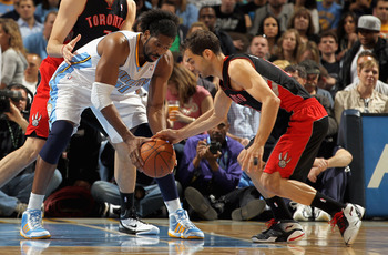 DENVER, CO - MARCH 21:  Jose Calderon #8 of the Toronto Raptors attempts to steal the ball from Nene #31 of the Denver Nuggets at the Pepsi Center on March 21, 2011 in Denver, Colorado. NOTE TO USER: User expressly acknowledges and agrees that, by downloa