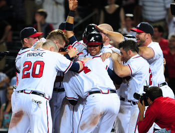 ATLANTA - JUNE 16: Diory Hernandez #24 of the Atlanta Braves is mobbed by teammates after scoring the winning run on a balk by the New York Mets at Turner Field on June 16, 2011 in Atlanta, Georgia. (Photo by Scott Cunningham/Getty Images)