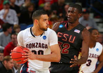 BUFFALO, NY - MARCH 19:  Robert Sacre #00 of the Gonzaga Bulldogs handles the ball agianst Solomon Alabi #32 of the Florida State Seminoles during the first round of the 2010 NCAA men's basketball tournament at HSBC Arena on March 19, 2010 in Buffalo, New