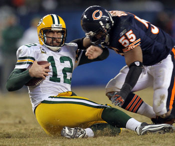 CHICAGO, IL - JANUARY 23:  Quarterback Aaron Rodgers #12 of the Green Bay Packers slides as he is hit by linebacker Lance Briggs #55 of the Chicago Bears in the NFC Championship Game at Soldier Field on January 23, 2011 in Chicago, Illinois.  (Photo by Ja